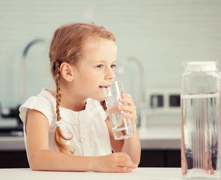 tomando agua: Child agua de vidrio. niña feliz en el país en la cocina