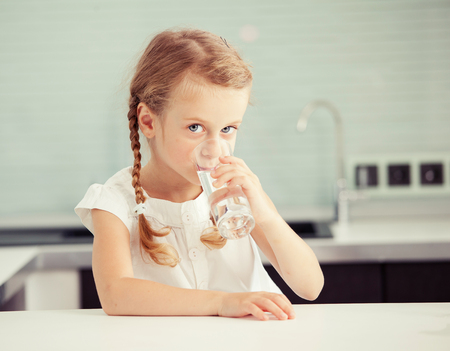 caucasian water drops: Child drinking water from glass. Happy little girl at home in kitchen