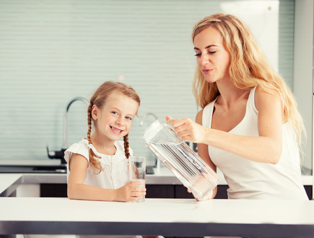 Child with mother drinking water from glass. Happy family at home in kitchen Stockfoto