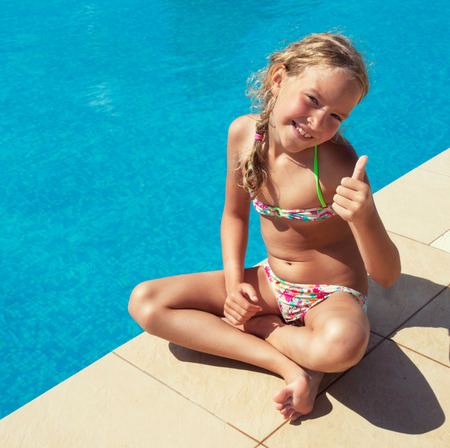 small girl: Happy child at pool outdoors. Girl playing at summer. Tourist Stock Photo