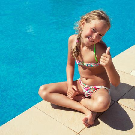 petite fille maillot de bain: Heureux enfant à la piscine en plein air. Fille jouant à l'été. Touristique
