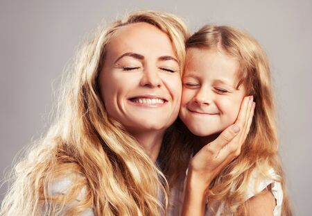 squint: Mother with little girl. Parent with child. Happy family clouse up squint Stock Photo