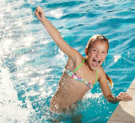 Glückliches Kind im Pool im Freien. Mädchen im Sommer zu spielen. Tourist