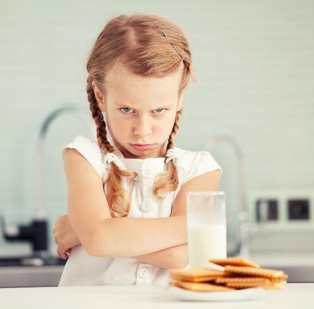 Kind schaut mit Ekel für Lebensmittel. Appetitlosigkeit. Kleines Mädchen, nicht wie Milch
