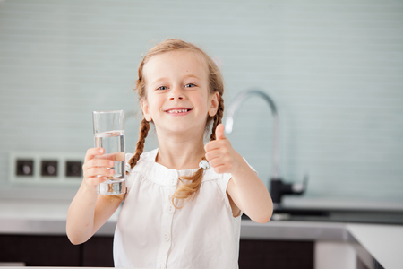 Child drinking water from glass. Happy little girl at home in kitchen