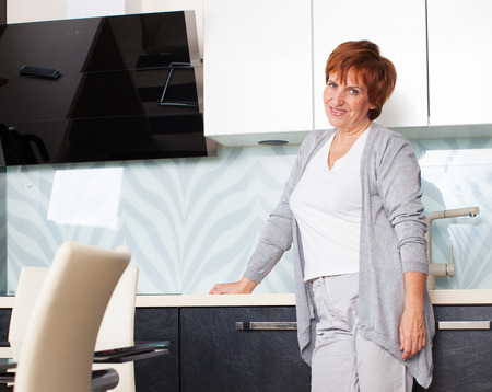 handcarves: Happy adult woman on kitchen. Mature female at home
