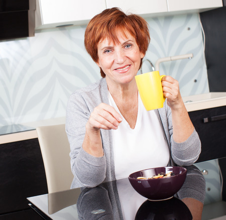 woman drinking tea: Happy adult woman on kitchen. Mature female at home