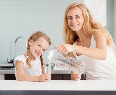 Child with mother drinking water from glass. Happy family at home in kitchen Stock Photo
