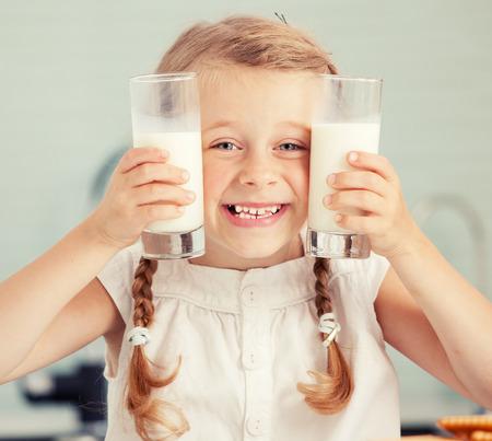tomando leche: Niño de beber la leche en casa. Niña feliz que come en casa