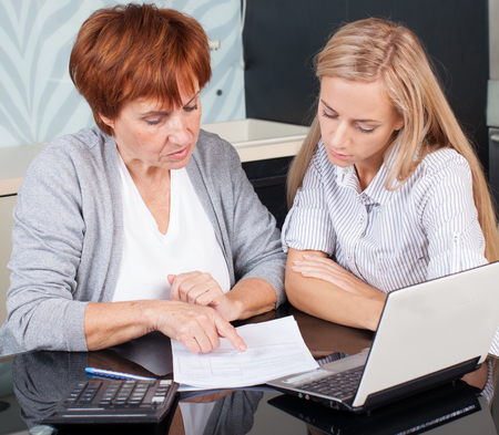 image consultant: Two women discussing documents at home. Consultant with woman