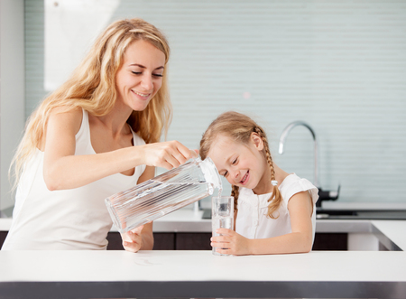 Child with mother drinking water from glass. Happy family at home in kitchen Archivio Fotografico