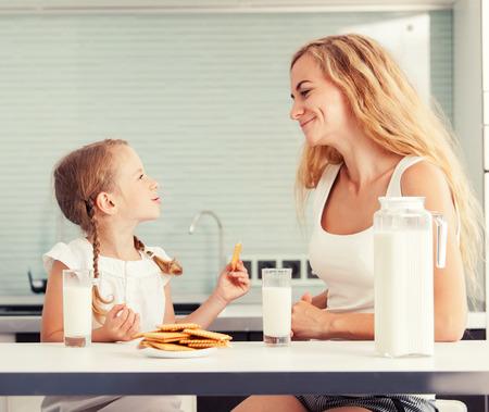 tomando leche: Niño con leche materna potable. Familia feliz que come en casa Foto de archivo