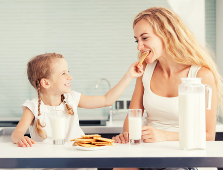 mother milk: Child with mother drinking milk. Happy family eating at home