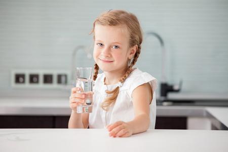 vaso con agua: Child agua de vidrio. niña feliz en el país en la cocina