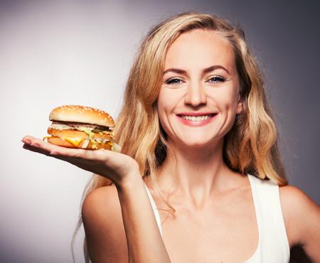 biting: Female with hamburger. Woman eating unhealthy food