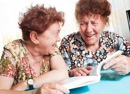 80 year old: Two seniors. Old woman reading book. Friendship elderly