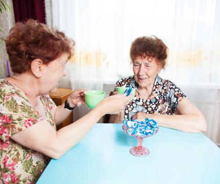 80 plus adult: Two seniors drinks tea. Old woman talking. Friendship elderly