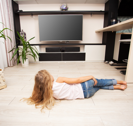 Child watching TV at home. Girl looking at television Stock Photo