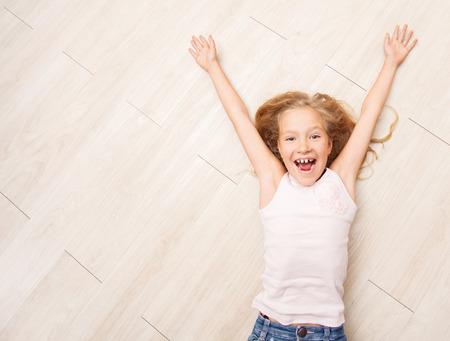 Child lying on floor heating. Girl on laminate, PVC tile Stockfoto