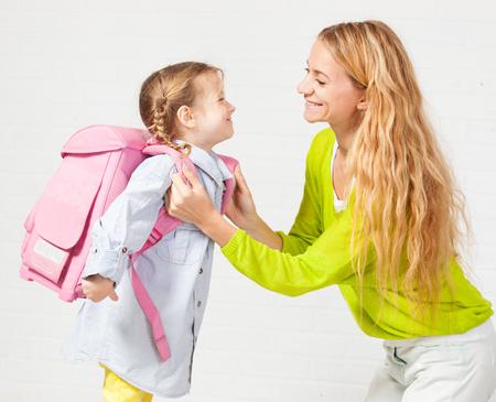 어머니는 딸이 학교에 다닐 준비를하도록 도와줍니다. 엄마가 아이가 배낭을 착용하도록 지원합니다. 스톡 콘텐츠