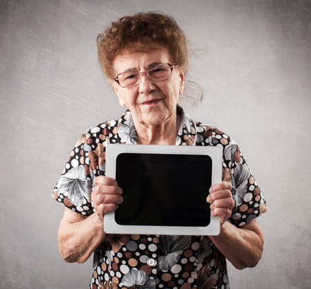 80 plus adult: Old woman holding a tablet in the hands of. Seniors with tablen pc Stock Photo