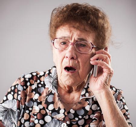 Surprised seniors talking mobile phone. Old adult mature woman. Shock Foto de archivo