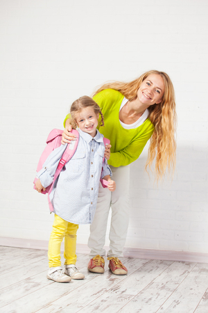 get ready: Mother helps her daughter get ready for school. Mom support child to wear a backpack