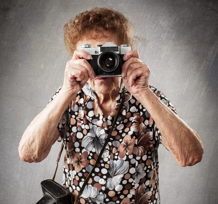 80 year old: Granny photographer. Old woman with camera. Senior studio shot