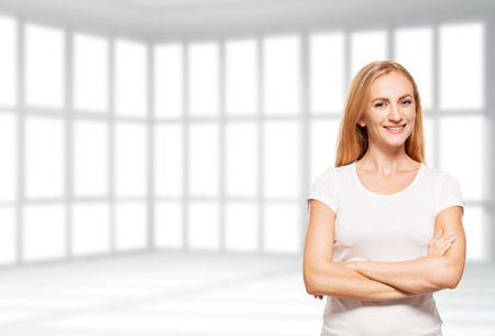 empty office: Happy businesswoman in empty office. Young smiling female in apartment