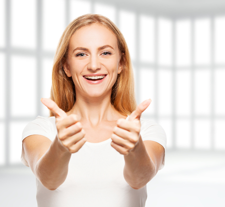 empty office: Happy businesswoman in empty office. Young smiling female in apartment showing sign ok