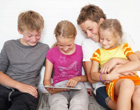 children only: Children with tablet. Group kids playing
