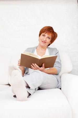 woman lying: Adult woman reading book at sofa. Stock Photo
