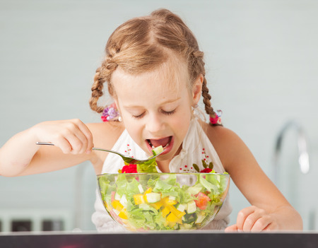 eating salad: Little girl eating vegetable salad in the kitchen.