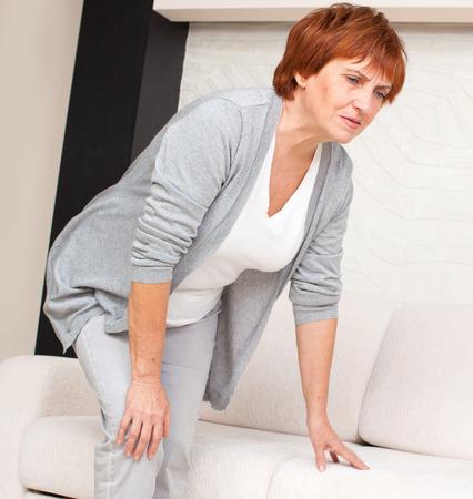 大人の女性には、膝の痛みがあります。成熟した女性の家に 写真素材