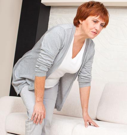 Adult woman has pain in the knee. Mature female at home Stockfoto