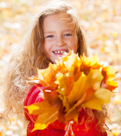 multi age: Girl at autumn. Child with leaf at park Stock Photo
