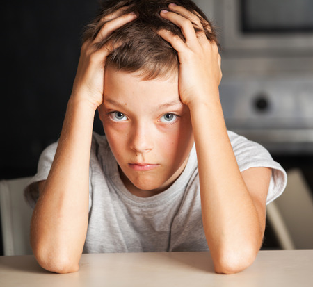 Sad boy at home. Unhappy abuse child. Emotions stress at teenager