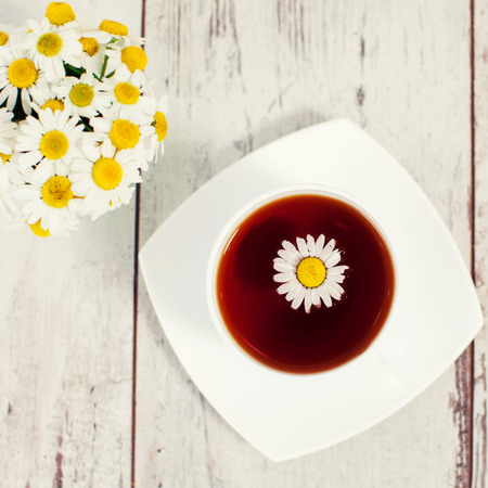 chamomile tea: Chamomile tea in a mug at wooden floor. Herbal natural healthful drink