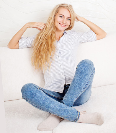 woman young: Happy young female on sofa. Smiling woman at home