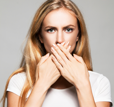 crooked teeth: Woman with closed mouth. Female covers her mouth with her hands. Silence, fear, violence. Stock Photo