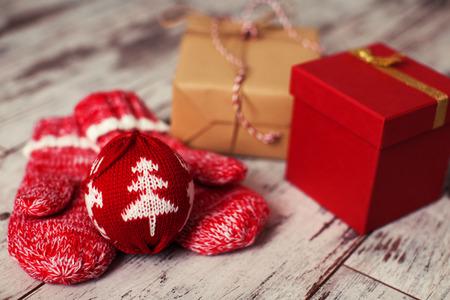Mitten with christmas ball on wood floor. Winter decoration Stock Photo