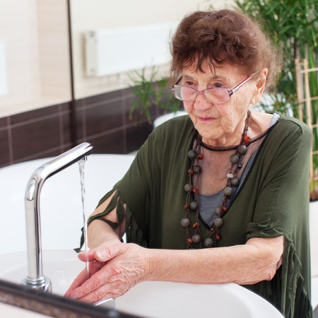 bathroom women: Elderly old woman washes her hands. Mature female at home