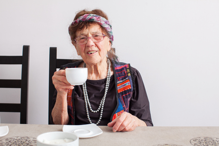 80 plus years: Old grandmother drinking tea. Granny woman at home. Mature female