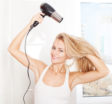 dry hair: Woman dry hair hairdryer at bathroom. Female with dryer at home