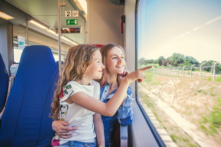 looking through window: Woman with child traveling by pablic transport. Family travelling in a train and looking through the window  Stock Photo