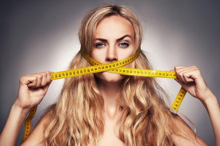 Vrouw die haar mond meting tape. Vrouw op een dieet