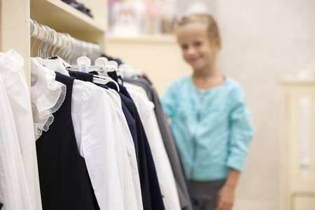 coathanger: Hanger with shirts in a store. Childrens clothing