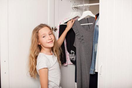 niños vistiendose: Niño elige la ropa del armario. Niña feliz