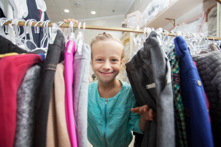 coathanger: Child in a childrens store. Happy girl choosing clothes Stock Photo