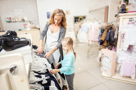 coathanger: Child with mother in a childrens store. Happy girl choosing clothes. Family are shopping